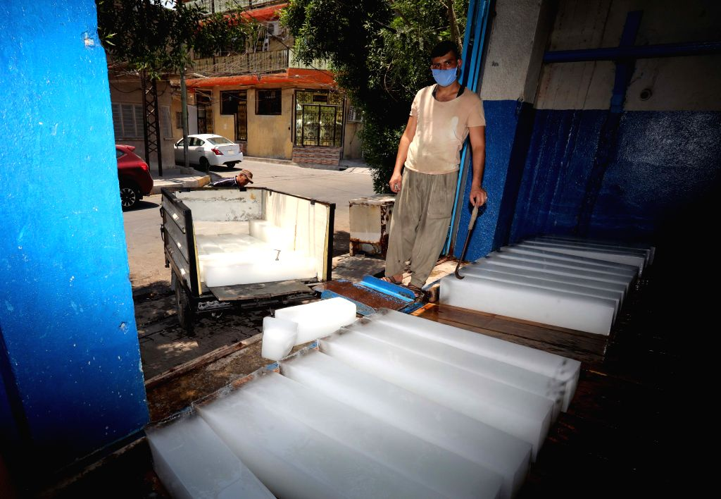 A man works at an ice-making workshop in Baghdad, Iraq, on July 5, 2020. As the temperature approaches 50 degrees Celsius in Baghdad, ice-making business here ...