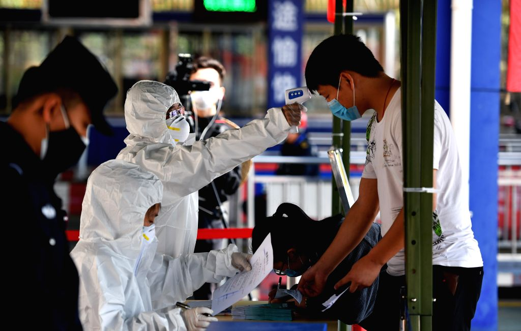 A medical staff member from Haikou of south China's Hainan Province measures body temperature of a passenger in Xuwen County of Zhanjiang City, south China's ...