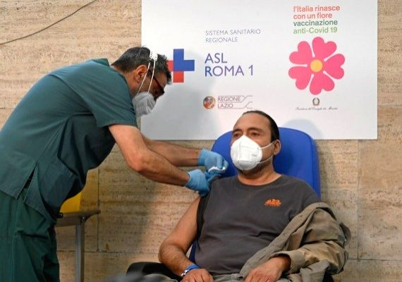 A medical worker administers a booster COVID-19 vaccine shot to a recipient at Santo Spirito hospital in Rome, Italy, Sept. 21, 2021.