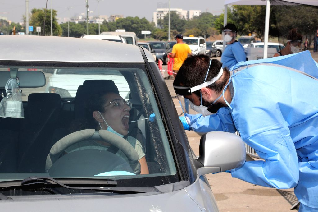 A medical worker collects a swab from a man for a COVID-19 test in Tel Aviv