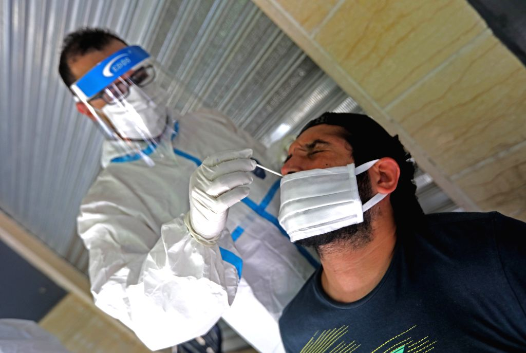 A medical worker conducts a polymerase chain reaction (PCR) test for COVID-19 in Beirut, Lebanon, July 14, 2020. Lebanon's number of COVID-19 infections increased on ...