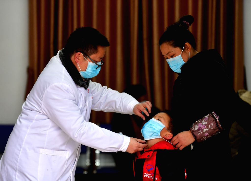 A medical worker demonstrates how to correctly use masks for prevention in Wuying, a village of Miao ethnic group on the border of south China's Guangxi Zhuang ...