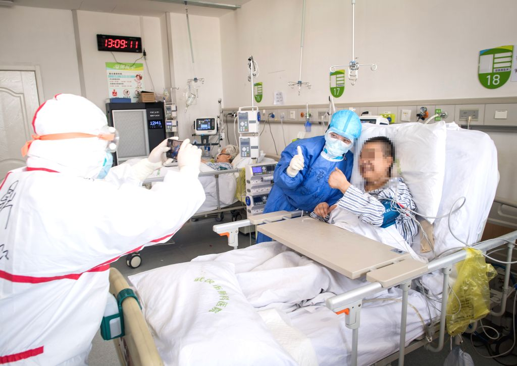 A medical worker from east China's Zhejiang Province and a patient infected with COVID-19 pose for a group photo at a ward of the Wuhan pulmonary hospital in Wuhan, ...