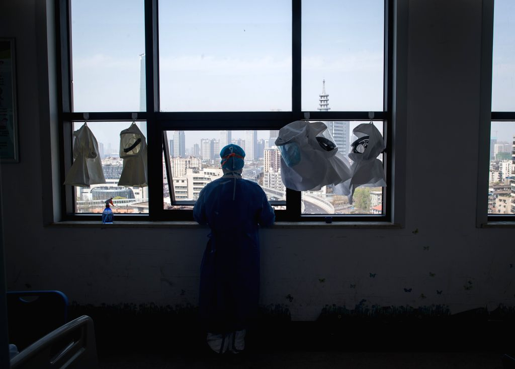 A medical worker from south China's Hainan Province rests by the window at the Wuhan pulmonary hospital in Wuhan, central China's Hubei Province, March 19, 2020. As ...