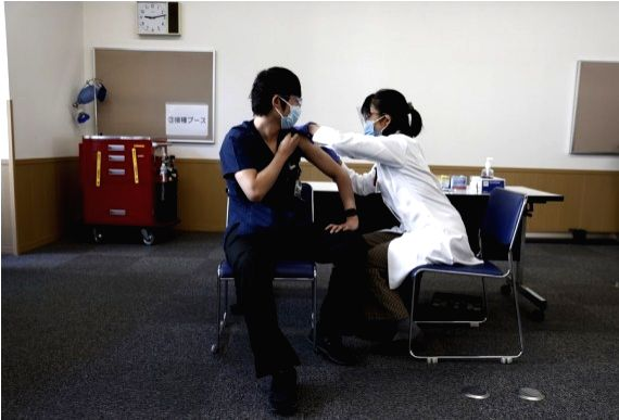 A medical worker receives a dose of COVID-19 vaccine as the country launches its inoculation campaign at Tokyo Medical Center in Tokyo, Japan, Feb. 17, 2021.