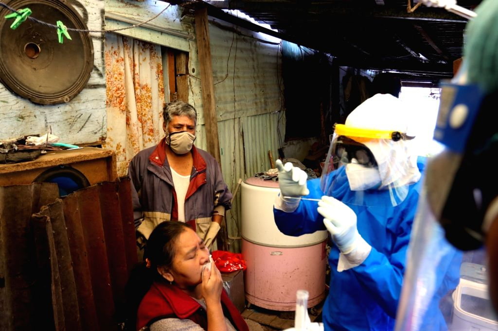 A medical worker takes a swab sample from a woman for COVID-19 test in Mexico City, Mexico, Aug. 13, 2020.   The total number of COVID-19 cases in Mexico has ...