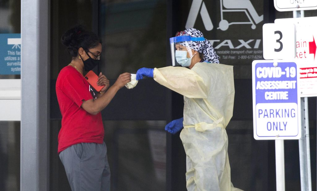 A medical worker wearing protective gear hands out a face mask to a woman outside a COVID-19 assessment center in Toronto, Canada, on Aug. 11, 2020. As of Tuesday ...