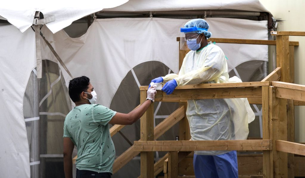A medical worker wearing protective gear helps a man register at a COVID-19 assessment center in Toronto, Canada, on Aug. 11, 2020. As of Tuesday evening, Canada ...