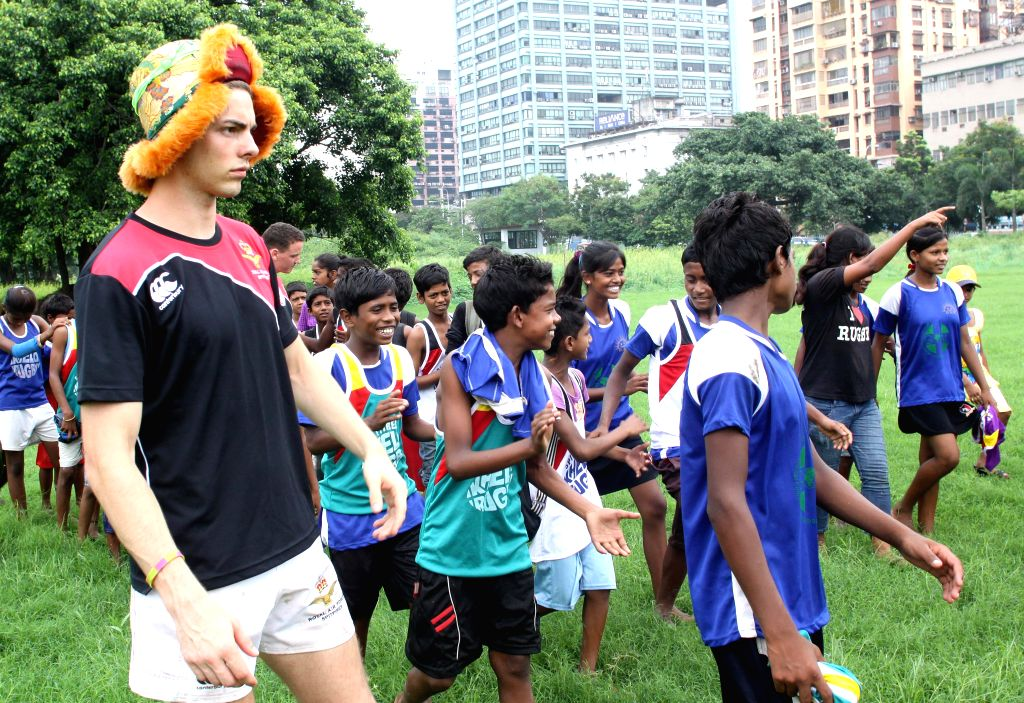 A member of British Royal Air Force (RAF) rugby union team teaches children to play rugby in Kolkata on June 20, 2014.