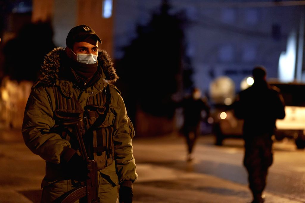 A member of Palestinian security forces stands guard outside a hotel under quarantine due to the COVID-19 outbreak, in Beit Jala, near the West Bank city of ...
