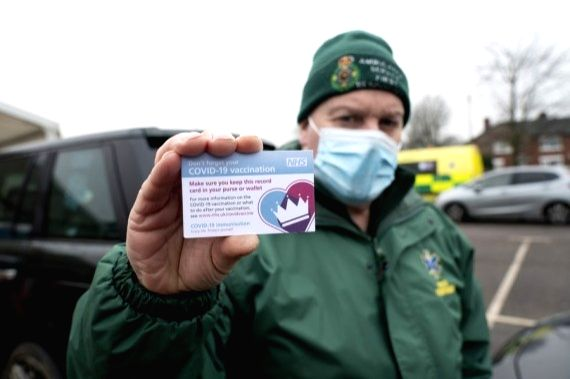 A member of staff holds vaccination record cards given to members of the public receiving their second dose of the Pfizer-BioNTech COVID-19 vaccine at Hyde Leisure Center in Greater Manchester, ...