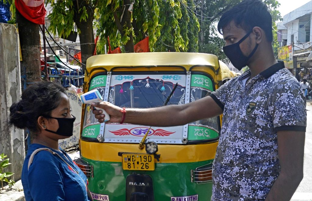 A member of the Auto Union screens passengers for COVID-19 before letting them board autos to their respective destinations, amid Unlock 1.0 or phased relaxation during the fifth phase of ...