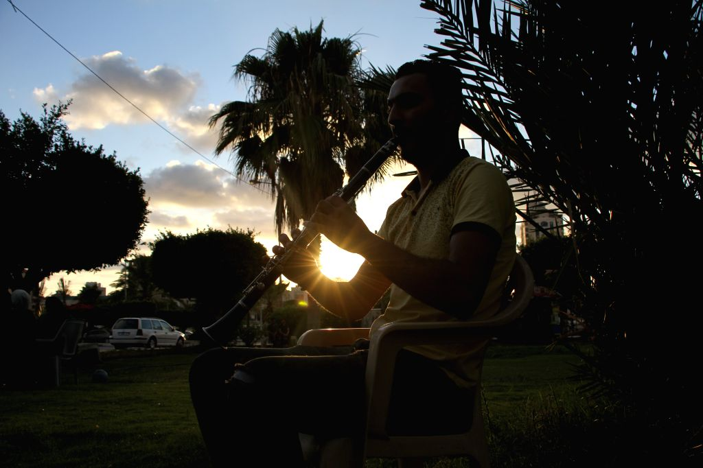 "A member of the Palestinian band ""Street Band"" performs at a park in Gaza City, on June 24, 2020. Every day, just before sunset, three Palestinian youths ..."