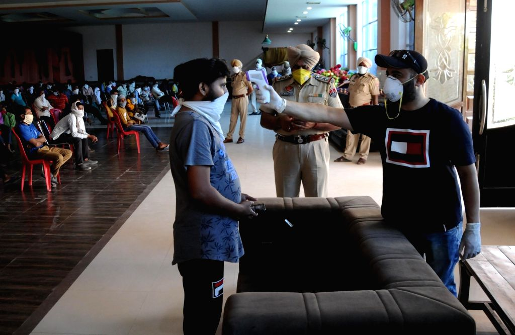 A migrant worker from Uttar Pradesh who was stranded in Punjab due to the ongoing nationwide lockdown imposed to mitigate the spread of coronavirus, undergoes COVID-19 screening before ...