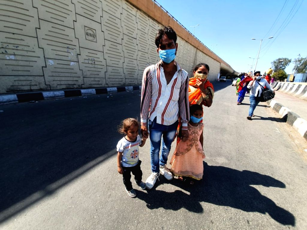 A migrant worker heading back home with his family, at Anand Vihar bus terminal close to Delhi's border with Ghaziabad on Day 5 of the 21-day countrywide lockdown imposed to contain the ...