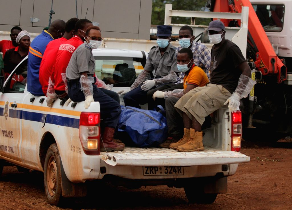 A miner's body is put on a pickup truck near a flooded shaft at a mine in Battlefields, Mashonaland West Province, Zimbabwe, Feb. 16, 2019. Eleven illegal ...