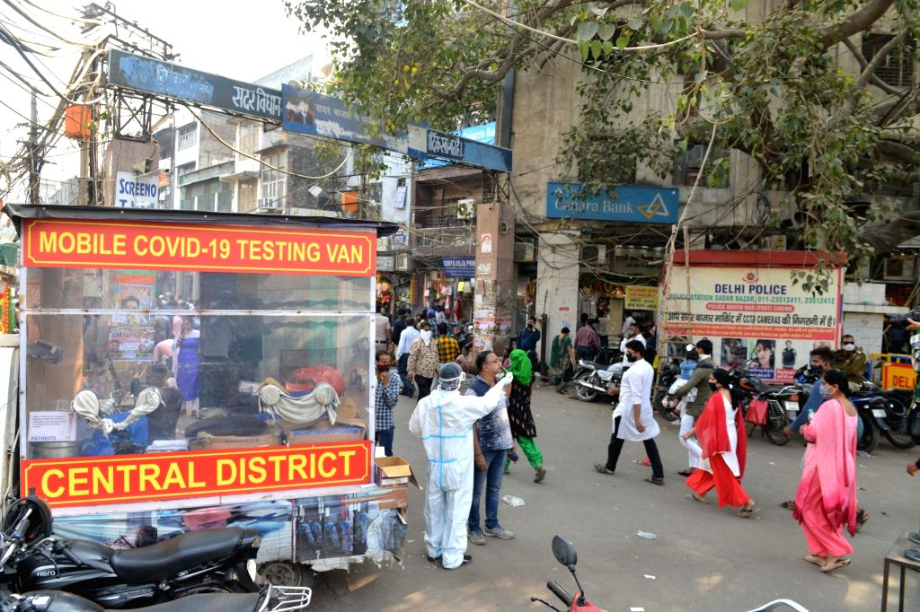 A mobile COVID-19 testing van collects samples from people for coronavirus testing, at a busy Delhi market on the eve of Diwali on Nov 13, 2020.