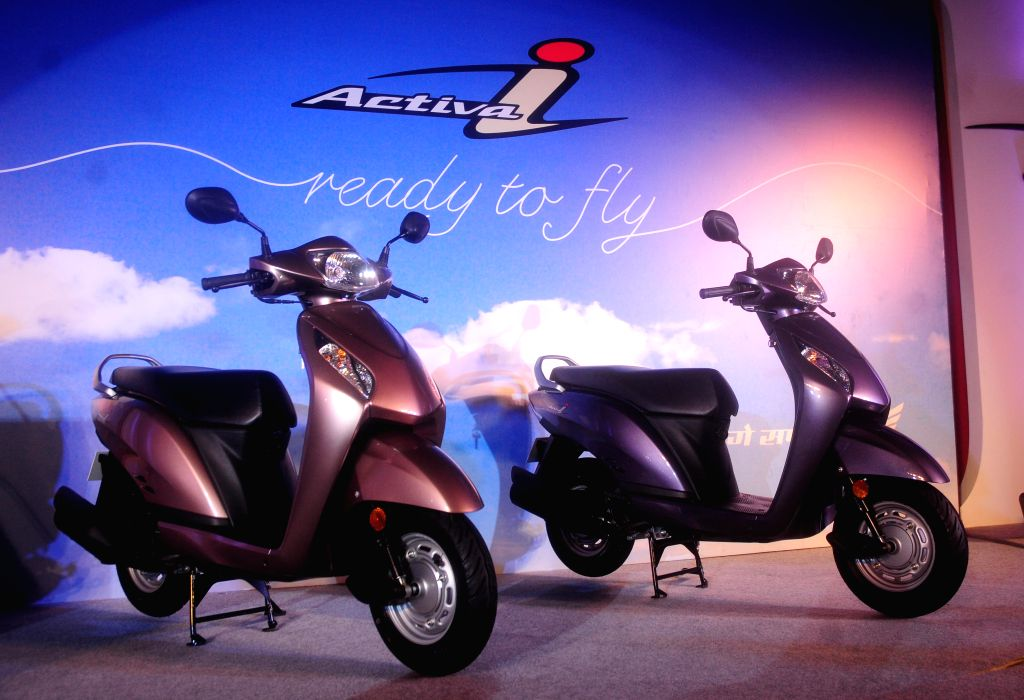 A  model poses with  Honda 'Activa-i' during its launch in New Delhi on June 12, 2013. (Photo: IANS)