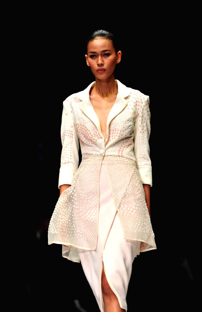 A model presents a creation by Indian designer Rahul Mishra during the first day of Jakarta Fashion Week in Jakarta, Indonesia, Oct. 24, 2015. ...