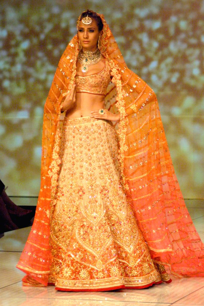 A model showcases fashion designer Tarun Tahiliani's creations during  `BMW India Bridal Fashion Week 2014` in New Delhi on Aug 7, 2014.