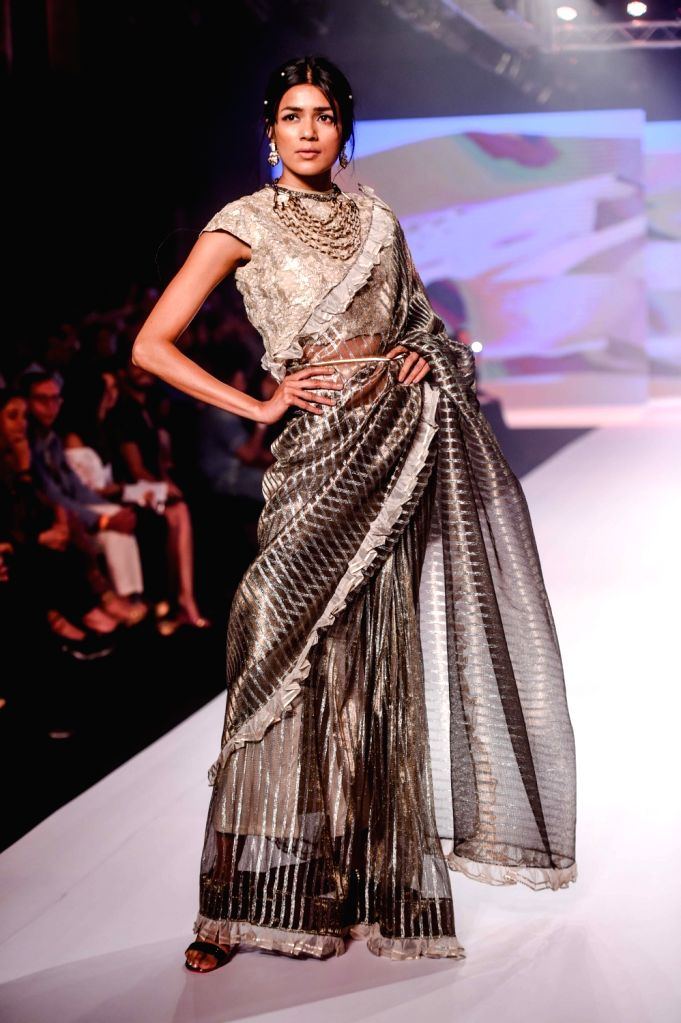 A model walks the ramp showcasing designers Rina Dhaka and Poonam Soni's creation on the second day of Bombay Times Fashion Week 2018, in Mumbai on March 31, 2018.