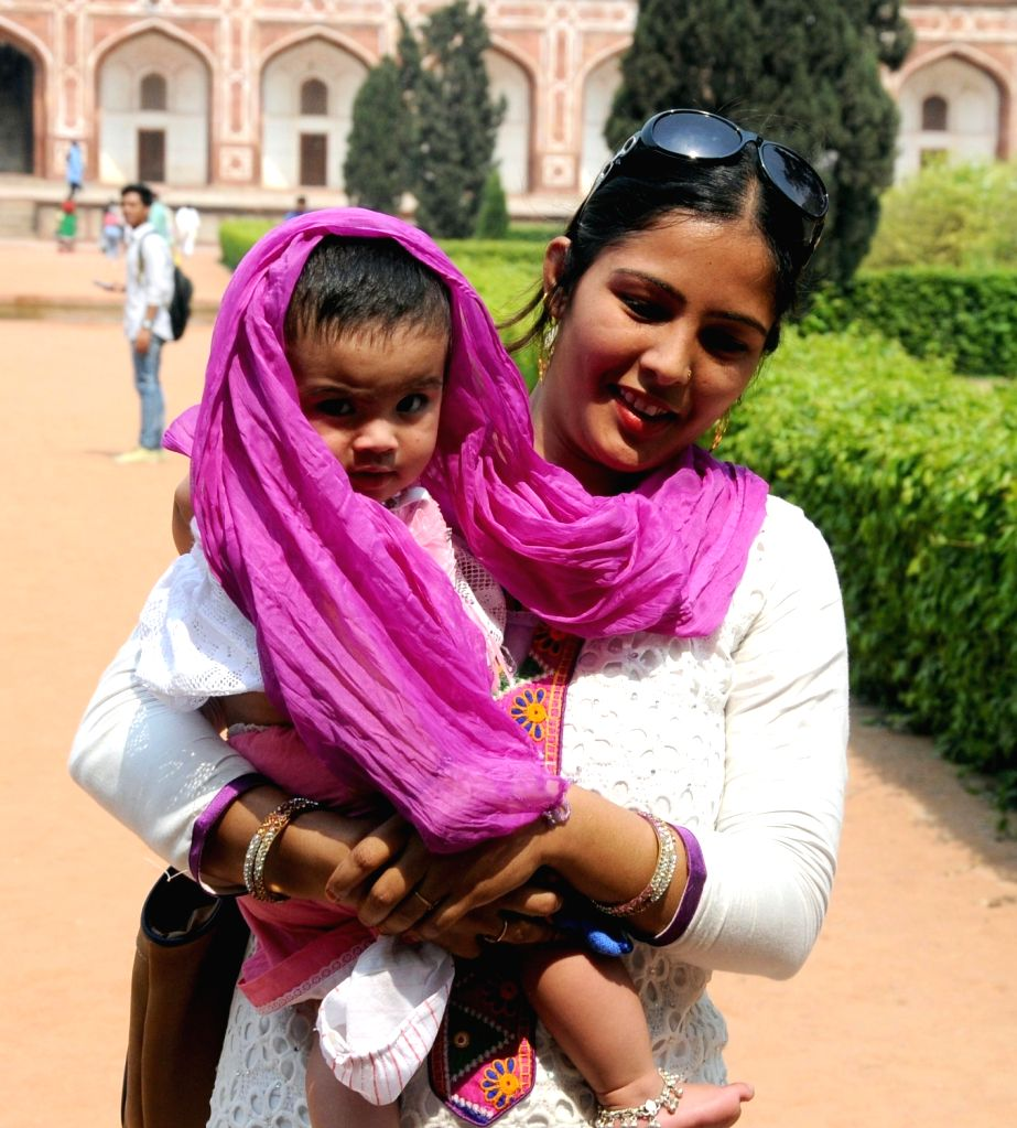 A mother covers her child with dupatta at Humayun's Tomb in New Delhi, on May 8, 2016. 8th May is observed as Mother's Day across the world.