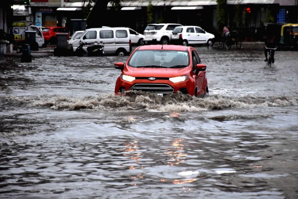 A motorist struggles through a water logged road of Jaipur on July 1,2016.