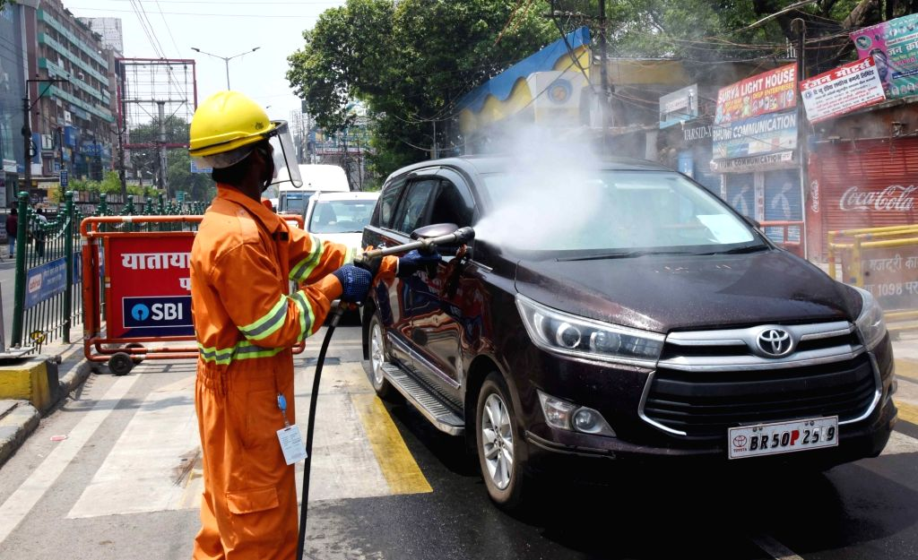 A municipal worker sanitises vehicles at Patna's Dak Bunglow Chowk during the extended nationwide lockdown imposed to mitigate the spread of coronavirus; on Apr 23, 2020.