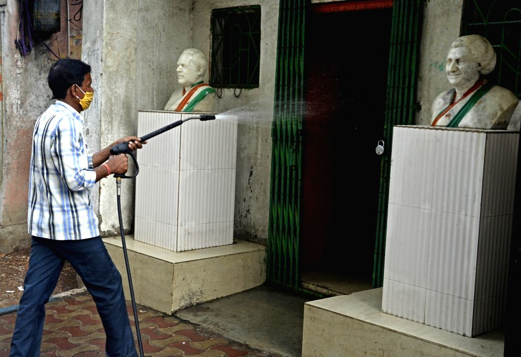 A municipal worker sprays disinfectants as part of a sanitisation drive being conducted across Kolkata during the extended nationwide lockdown imposed to mitigate the spread of coronavirus; ...