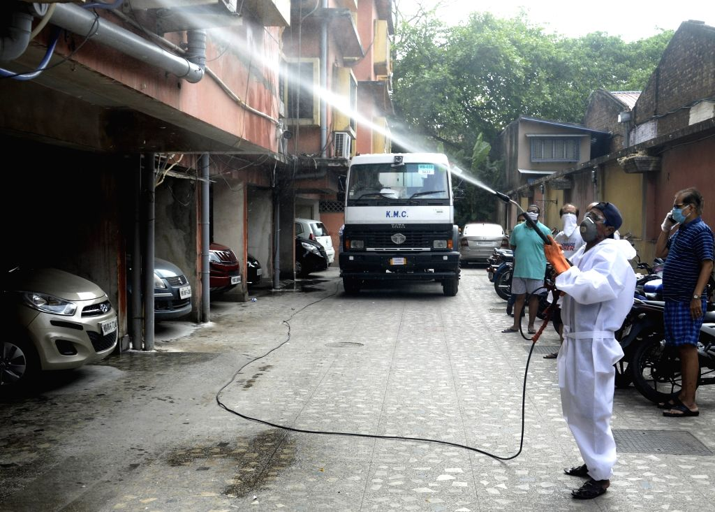 A municipal worker wearing Personal Protective Equipment (PPE) suit sprays disinfectants as part of a sanitisation drive being conducted across Kolkata during the extended nationwide ...