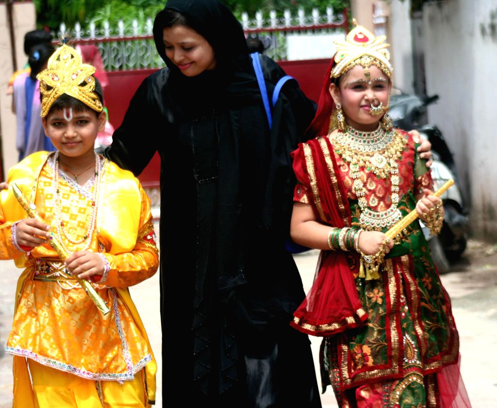 A muslim woman with her kids dressed as Lord Krishna and Radha returning home after a school competition on the eve of Janmastami in Varanasi on Aug. 16, 2014.