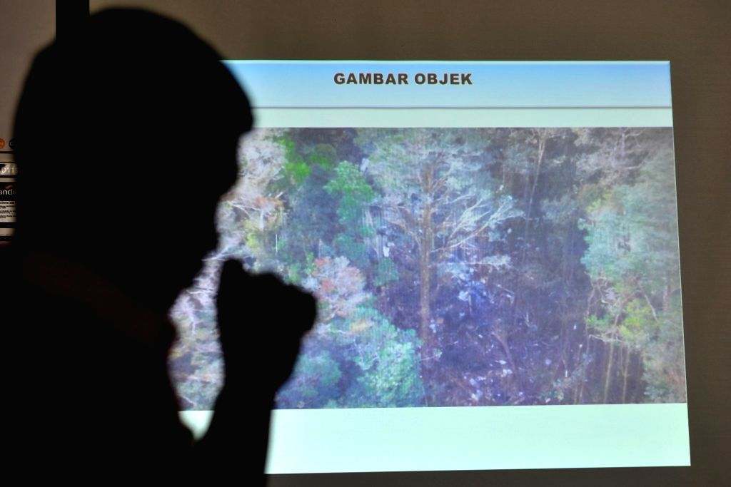 A National Search and Rescue Agency (Basarnas) staff member operates a big screen showing the location of the wreckage of a missing passenger plane during a press ...