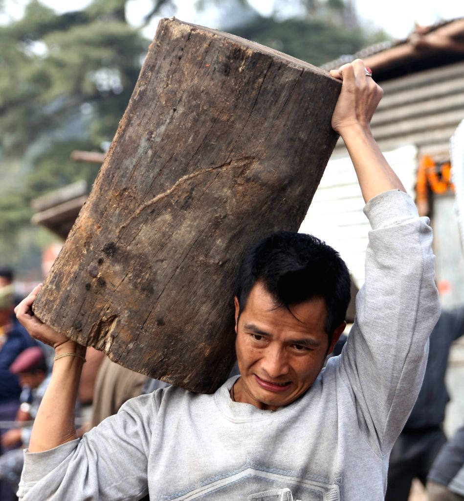A Nepalese man carries firewood sold by the government in Kathmandu, Nepal, Nov. 15, 2015. Nepal government sold firewood to the public to ease the ongoing fuel ...