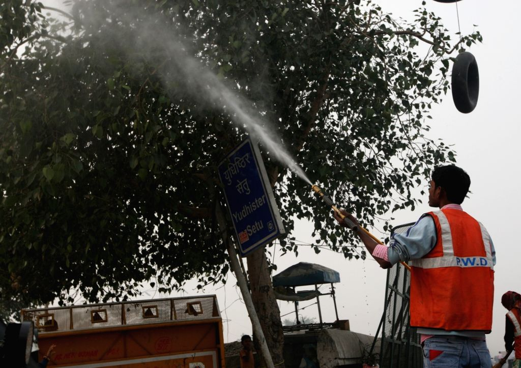 A New Delhi Municipal Corporation (NDMC) worker sprinkles water on a tree to reduce dust particles, as a measure to curb pollution in New Delhi, on Nov 5, 2018.