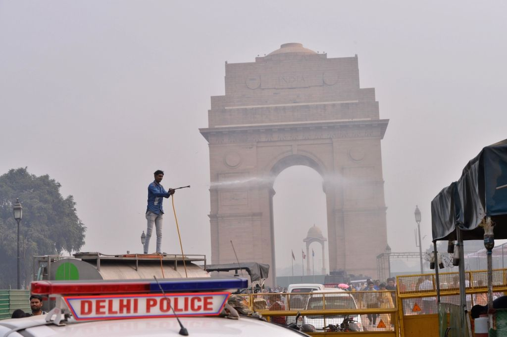 A New Delhi Municipal Corporation (NDMC) worker sprinkles water on a street at India Gate as a measure to curb pollution in New Delhi, on Nov 5, 2018.