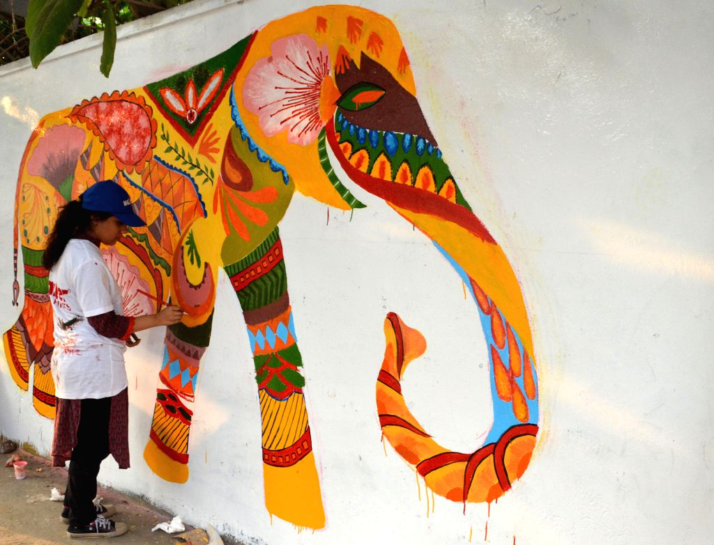 A Pakistani art student decorates a wall along a street in eastern Pakistan's Lahore on Nov. 22, 2015.