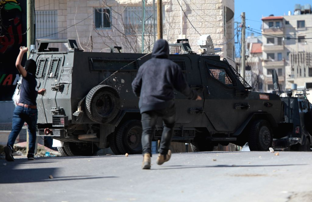 A Palestinian hurls stones at Israeli soldiers during clashes following a raid in search of a suspect wanted for a car-ramming attack earlier in Jerusalem that ...