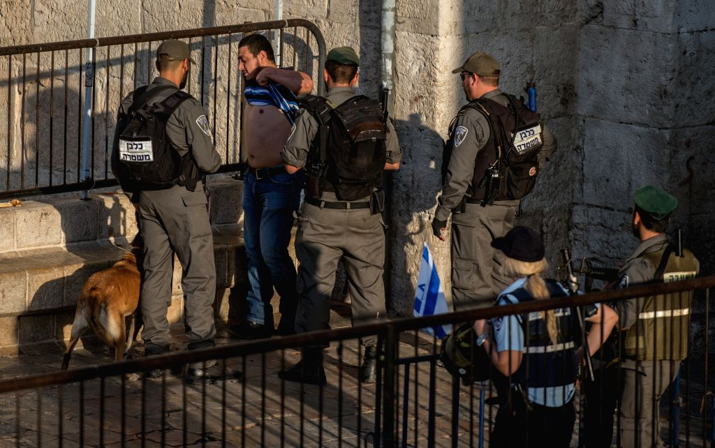A Palestinian is frisked by Israeli border police at Damascus Gate in the Old City of Jerusalem, on Oct. 16, 2015. Five Palestinians were killed on Friday in the ...