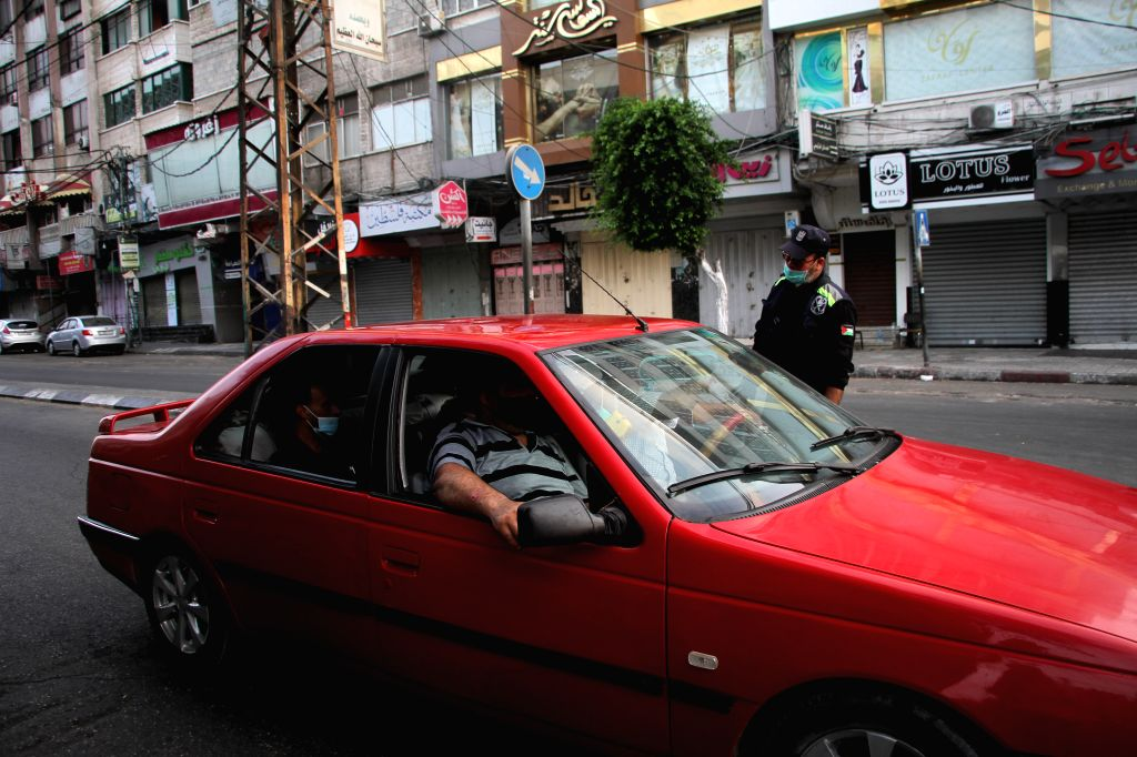 A Palestinian policeman checks a vehicle at a checkpoint during the lockdown to curb the spread of COVID-19 in Gaza City, on Aug. 30, 2020. Palestine on Sunday ...