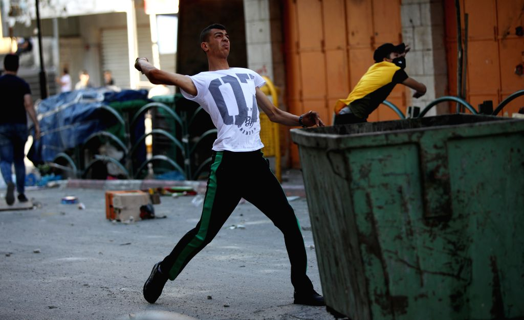 A Palestinian protester hurls stones at Israeli soldiers during clashes after a protest against the Israeli annexation plan in the West Bank city of Hebron, on July ...