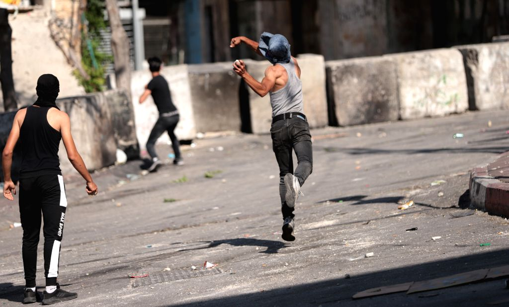 A Palestinian protester hurls stones at Israeli security members during clashes following a protest against the Israeli annexation plan, in the West Bank city of ...