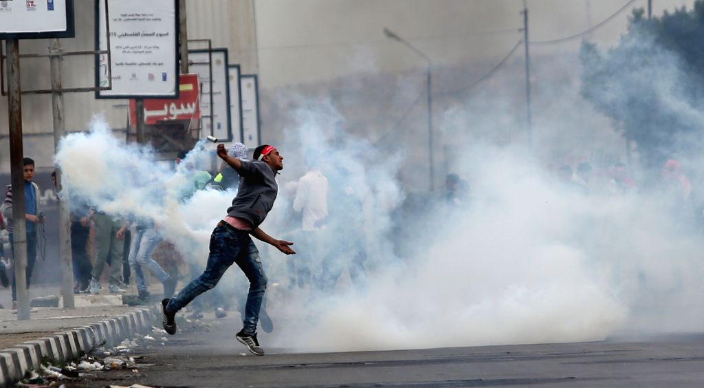 A Palestinian protester throws a tear gas canister back to Israeli troops during clashes at Hawara checkpoint near the West Bank city of Nablus, Nov. 28, 2015. ...