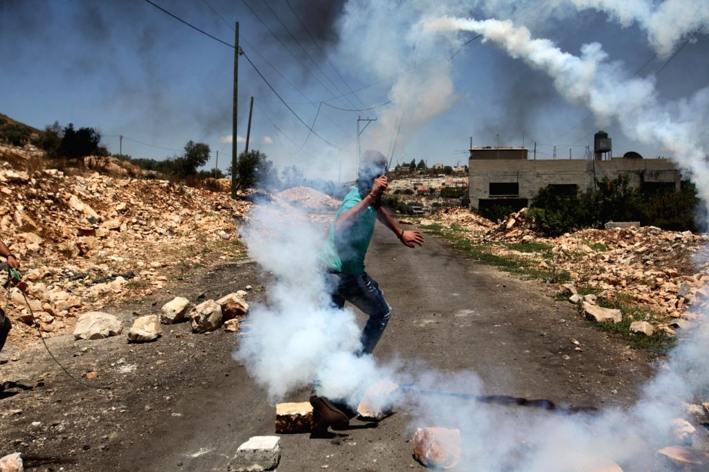 A Palestinian protester throws back a tear gas canister fired by Israeli soldiers during clashes after a protest against the expanding of Jewish settlements in Kufr Qadoom village near the ...