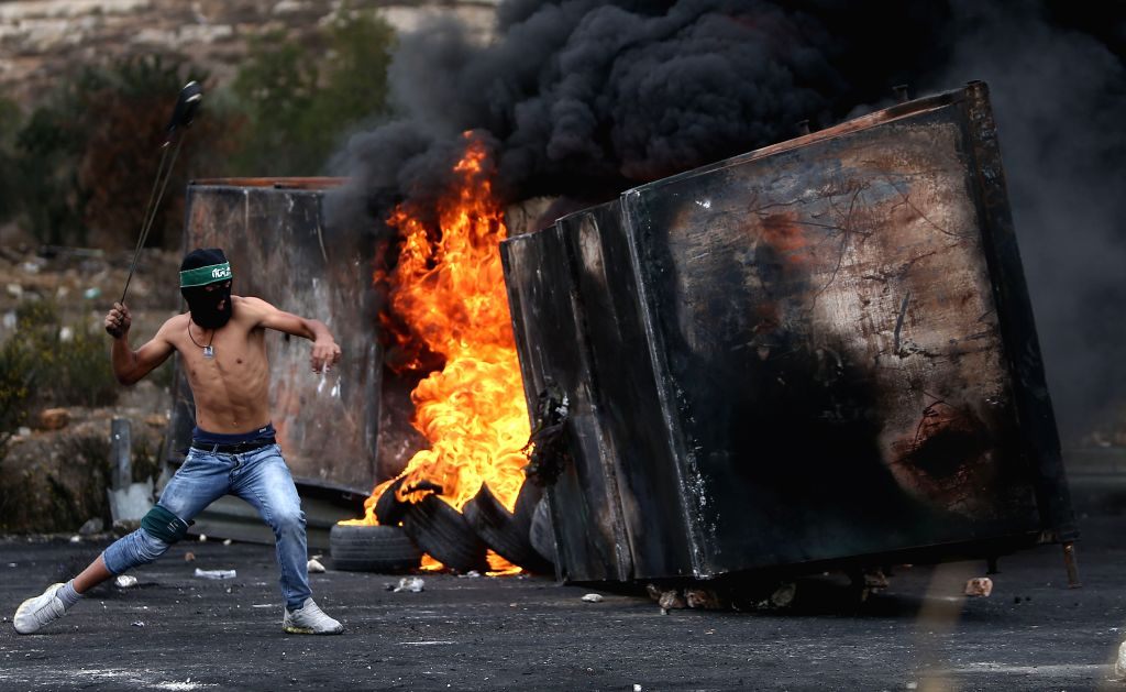 A Palestinian protester uses a slingshot to throw stones towards Israeli soldiers, during clashes in Beit El, on the outskirts of the West Bank city of Ramallah, ...