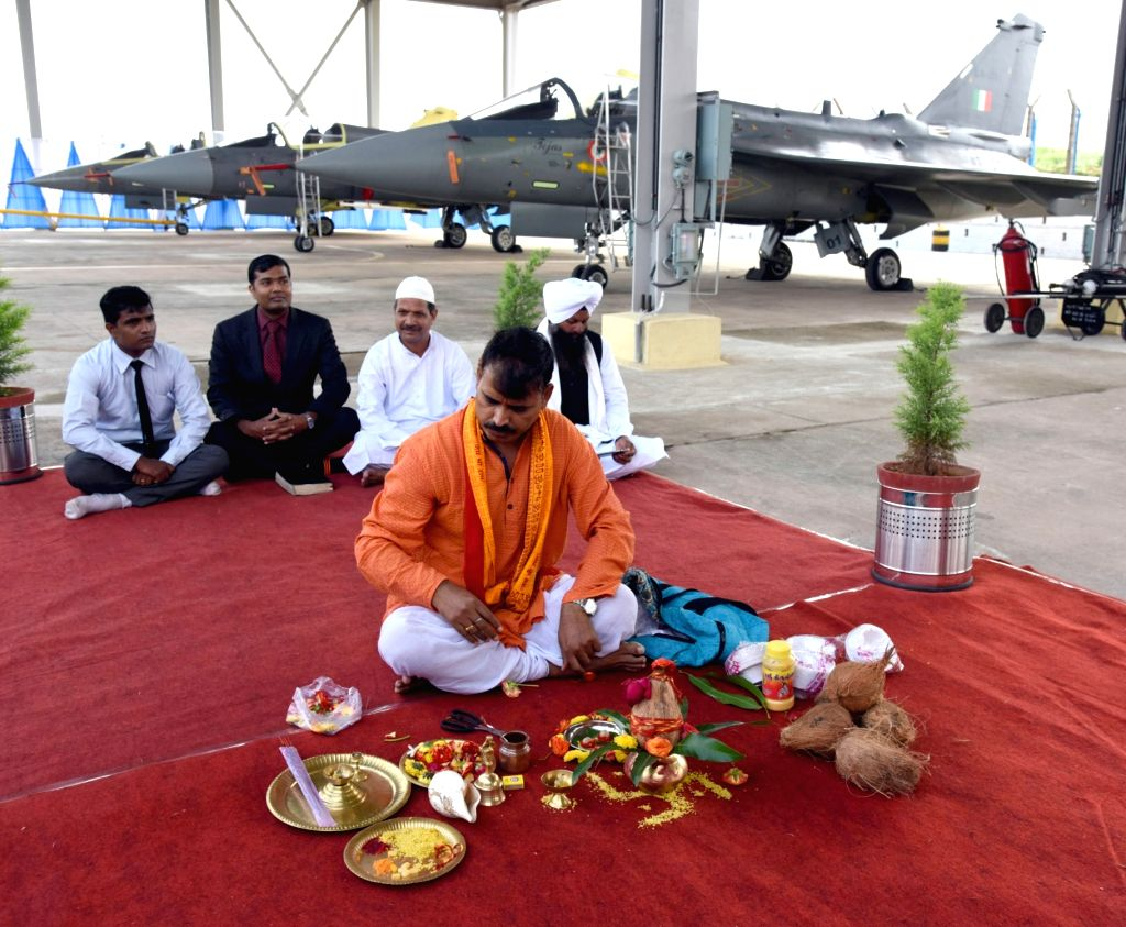 A pandit offers a pooja during the Tejas Light Combat Aircraft (LCA) induction ceremony at HAL, in Bengaluru on July 1, 2016.