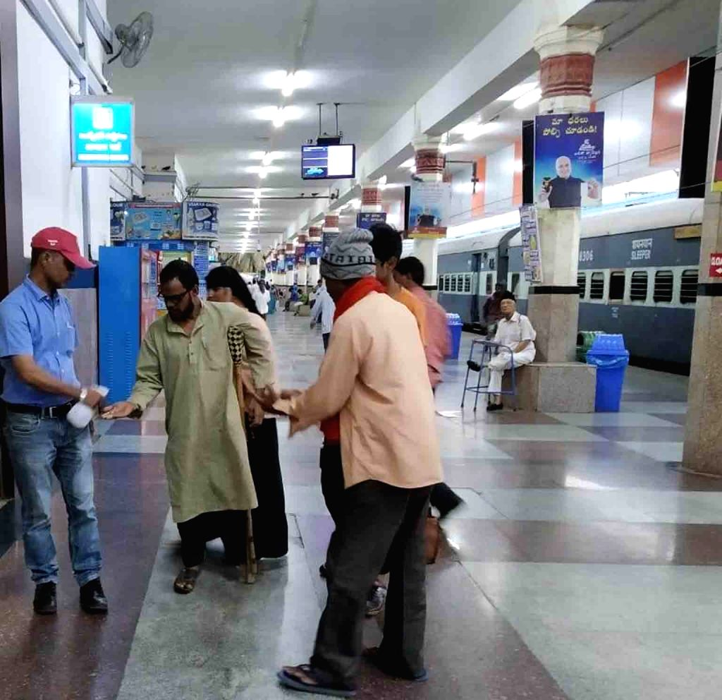 A passenger being provided with hand sanitiser amid COVID-19 pandemic, at the Secunderabad Railway Station in Hyderabad on March 16, 2020.