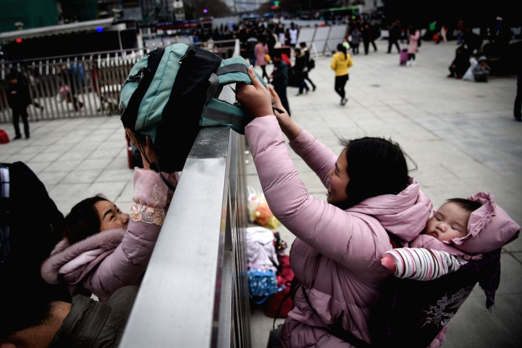 A passenger with her child passes baggage at Guiyang Railway Station in Guiyang, capital of southwest China's Guizhou Province, Jan. 13, 2017. About 2.98 billion trips are expected to be made ...