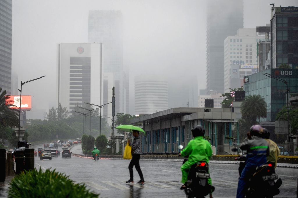 A passenger with umbrella crosses a street as fog covers the buildings along the main street in Jakarta, Indonesia, on Jan. 24, 2020.
