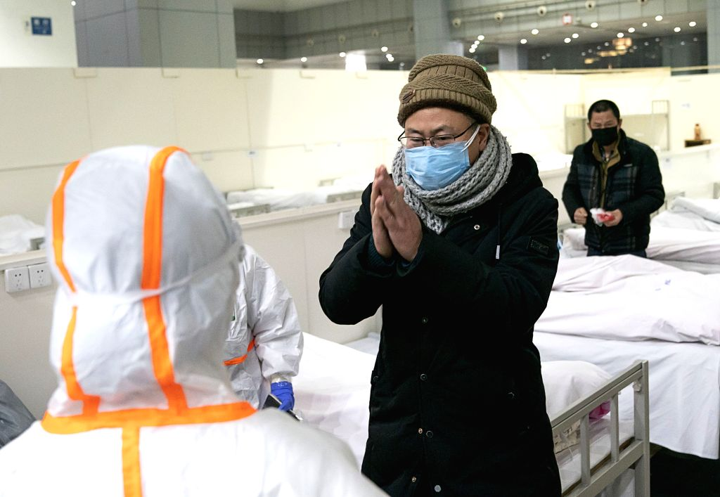 A patient infected with the novel coronavirus expresses gratitude to medical staff at a makeshift hospital converted from an exhibition center in Wuhan, central ...