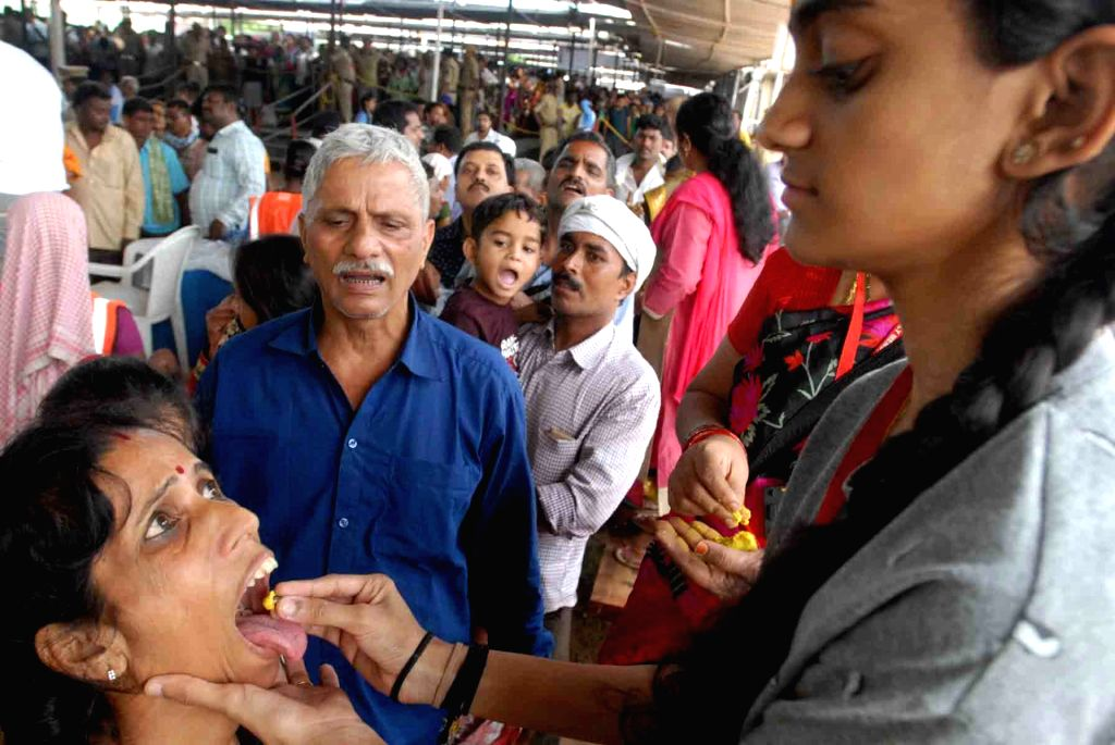 A patient receives fish medicine (Bathini Mrugasira Fish) at Exhibition Grounds, Nampally in Hyderabad on June 8, 2018. A yellow herbal paste is stuffed inside the fishes and are pushed ...